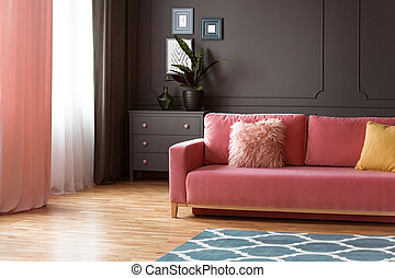 Pink couch with pillows in spacious grey living room interior with plant on cabinet. Real photo