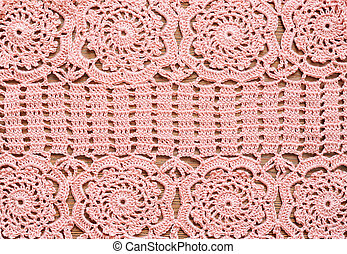 Pink crochet lace on a wooden surface