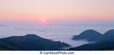 Pink dawn above the clouds in the mountains