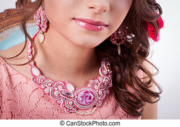 pink decoration technique soutache a girl in a pink dress, earrings and necklaces