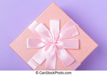 Pink decorative gift box with bow on purple background