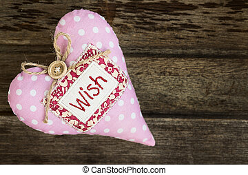Pink dotted handmade fabric heart with word WISH on wooden background, top view