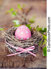 Pink easter egg in nest