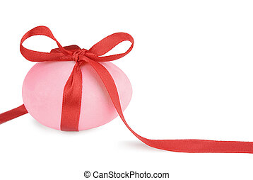 Pink Easter egg with a red ribbon isolated on white...
