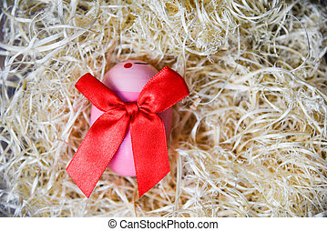Pink easter eggs with red ribbon bow in the nest on background top view
