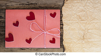 pink envelope and little heart on wood table for Valentines Day