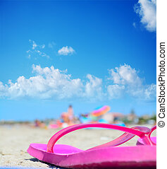flip flops under a blue sky with clouds