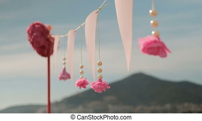 Pink flowers and beads hang like a decoration for a summer holiday.