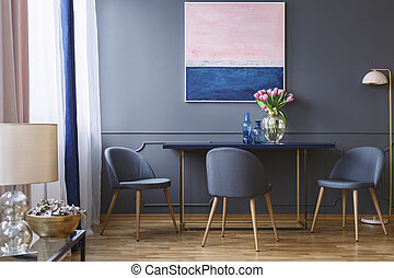 Pink flowers on table in dining room interior with painting and grey chair next to lamp. Real photo