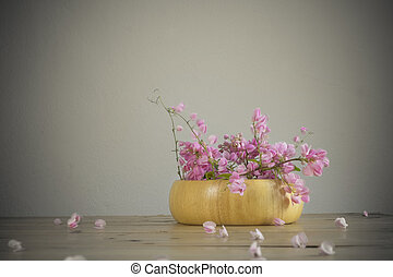 Pink flowers on wooden table over grunge background