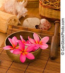 Pink frangipani with pebbles on woven bamboo mat