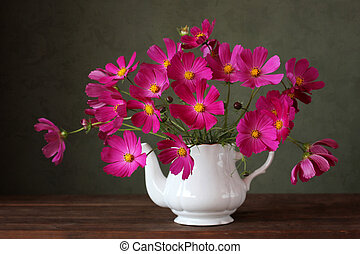 pink garden flowers in a teapot on a green background.