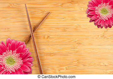 Gerber Daisy and Chopsticks on a Bamboo Background