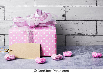 Pink gift box and blank brown paper tag with pink heart