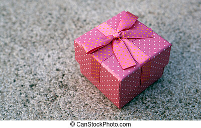 pink gift box with a bow on a gray marble slab