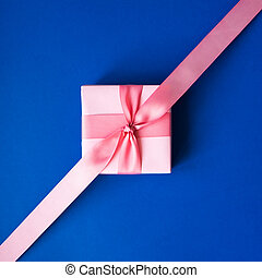Pink gift box with a pink ribbon on a blue background .