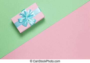Pink gift box with blue bow on pastel two-color background pink and green, copy space, flat lay. March 8, February 14, birthday, St. Valentine's, Mother's, Women's day celebration concept. Horizontal
