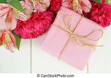 Pink gift box with pink carnation and lily flowers against white wood