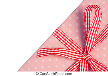 Pink gift wrapped present with gingham ribbon on white ...