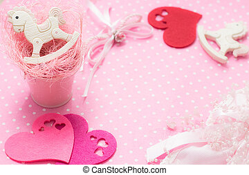 Pink girl party baby theme with ponies and hearts on felt background. Copy space