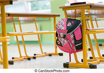 Pink girly school bag and pencil case on a desk in an empty classroom. First day of school concept.