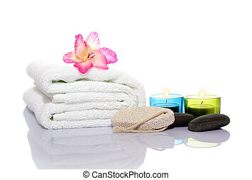 Pink gladiola, towel, candles and river stones