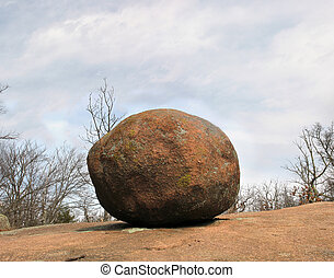 A large, round, lichen covered pink granite boulder rests on top of a hill with trees in the background in Elephant Rocks Missouri State Park.