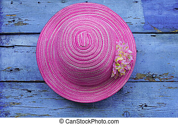 pink hat hanging on wooden wall