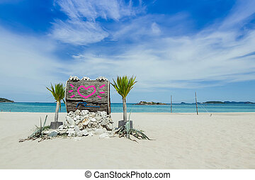 Pink heart drawn on Wooden board on the beach