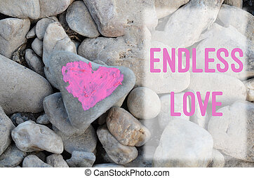 Pink heart painted with lipstick on piece of stone on background of many small stones with text letter Endless love.
