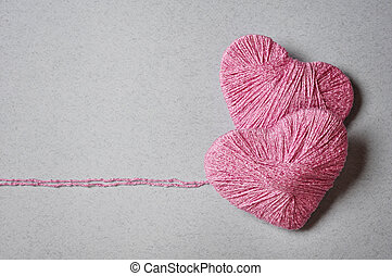 Pink heart shape made from wool on grey background