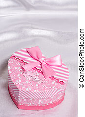 Pink heart shaped gift box with bow over white satin