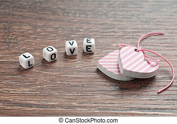 pink hearts on wooden board with letters love
