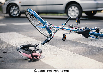 Pink helmet and blue kid's bike on a pedestrian lines after crash with a car