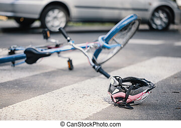 Pink helmet and blue kid's bike on pedestrian crossing after incident with a car