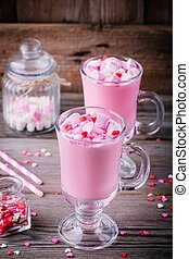 Pink hot chocolate with marshmallow and sugar hearts in a glass mug for Valentine Day
