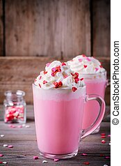 Pink hot chocolate with whipped cream and sugar hearts in a glass mug for Valentine Day