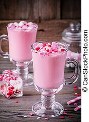 Pink hot milk with marshmallow and sugar hearts in a glass mug for Valentine Day