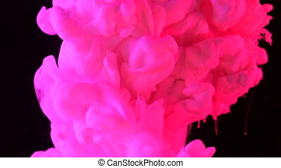 Pink ink in black underwater. Colour magenta paint reacting in water creating abstract cloud formations. Can be used as transitions, added to modern projects, art backgrounds.
