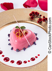 Pink jelly cake in heart shape with red berries and chocolate on white platter