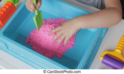 Pink kinetic sand and hands