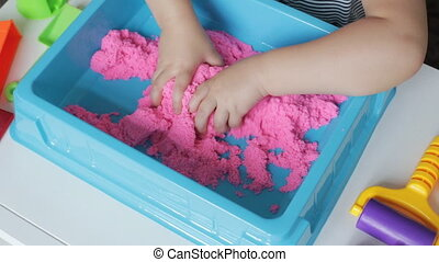 Pink kinetic sand. Little girl hands playing with Kinetic...
