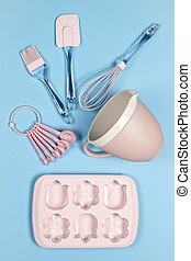 Pink kitchen backing utensils on blue background, top view