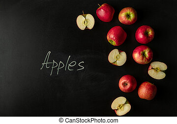 Pink lady apples on black background with text