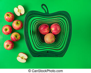 Pink lady apples on vibrant green background. Health concept
