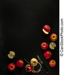Pink lady apples, some cut with knife on black background with copy space