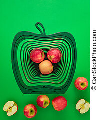 Pink lady red apples on vibrant green background. Health concept