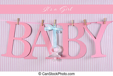 Pink letters bunting spelling Baby hanging from pegs on a line with dummy pacifier for Baby Girl shower or newborn.
