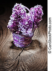 pink lilac flowers in small wicker basket on vintage wood