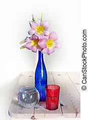Pink lilies in a blue vase on a white background